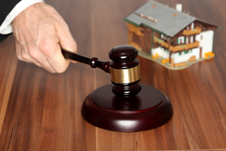 repossession: hammer on wooden table with house model in background