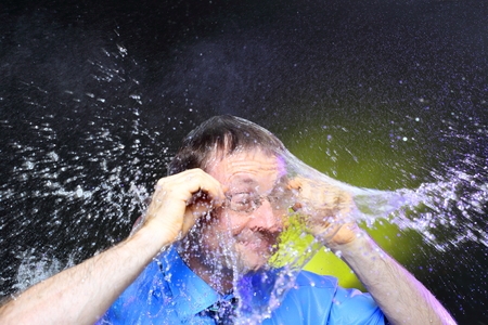rain wet: businessman with glasses is showering with water