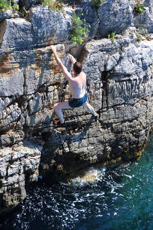 railey: climber is climbing up on cliffs over the ocean