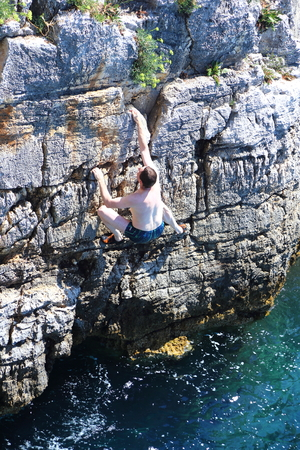 man is climbing up a cliff over the ocean Stock Photo