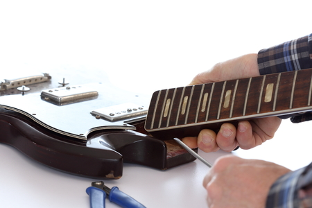 humbucker: a man is repairing an old electric guitar