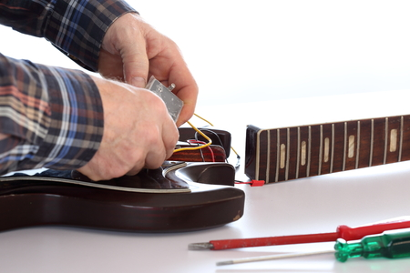 worker is repairing an old electric guitar