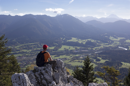 summer sport: hiker is sitting on a rock in the bavarian alps Stock Photo