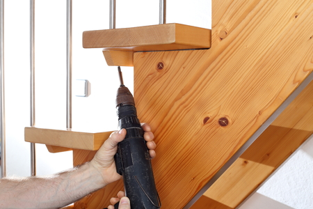 handrail: worker is fitting wooden stairs with handrail