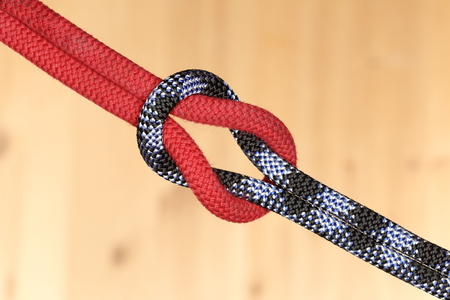 slipped: different ropes with knot on wooden plate Stock Photo