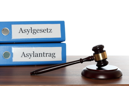 naturalization: gavel on board with asylum folders in background Stock Photo