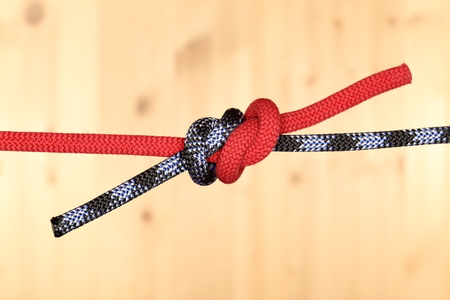slipped: two ropes with two knots on wooden background