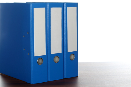 file folders: three blue file folders on desk in a row Stock Photo