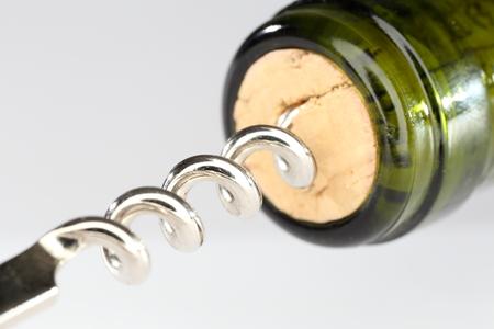 cork screw: wine bottle with cork screw on grey background