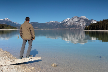 water's edge: man stands on waters- edge of a lake