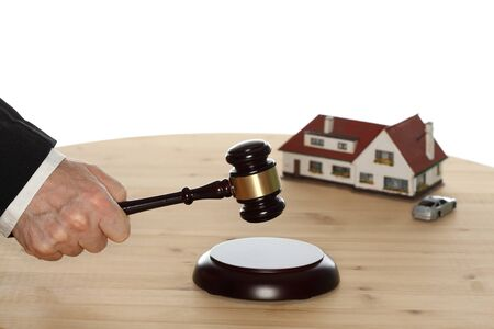 auctioneer: auctioneer with gavel in hand and house in background
