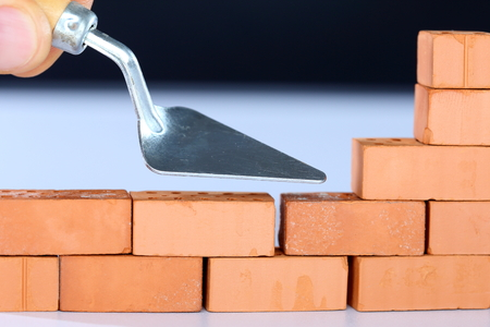 build up: to build up a brick wall with tool