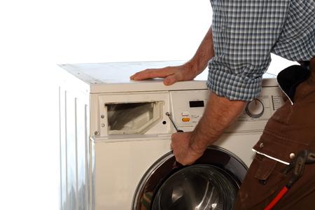 lavadora con ropa: electricista está trabajando en una lavadora de ropa Foto de archivo
