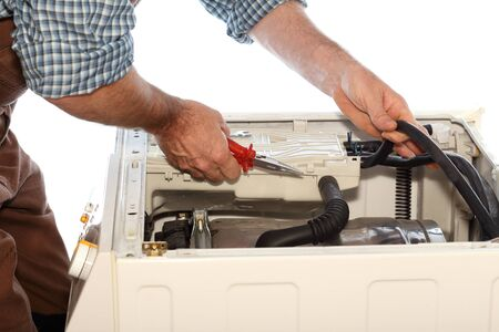 clothes washer: man is fixing a problem on a clothes washer