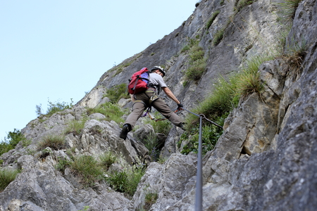 a man is climbing on a wall in nature Stock Photo