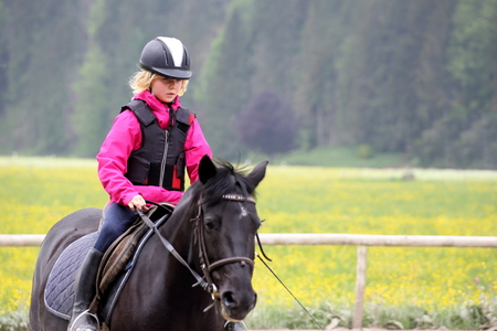 girl is concentrated and riding with a black horse Stok Fotoğraf