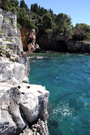 young girl is jumping from a high cliff