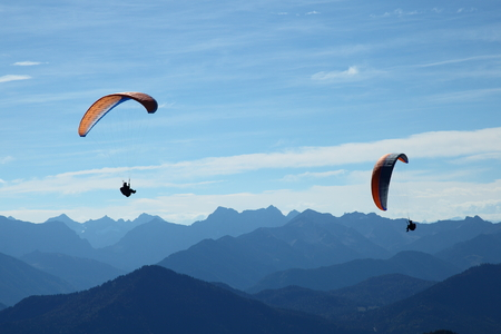 two paragliders flying in blue mountain landscape