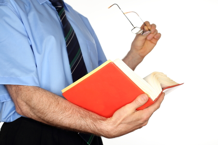 businessman is looking in a book with glasses in ahnd