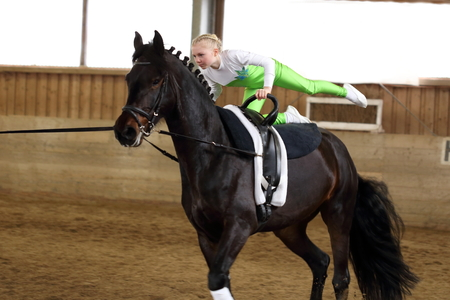 young girl is vaulting on a black horse Stock Photo