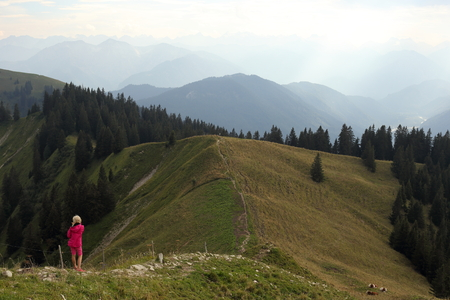 young hiking girl on a small mountain path photo