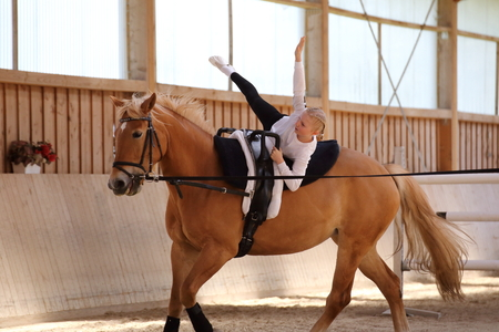 vaulting exercise, girl makes a star on horse photo