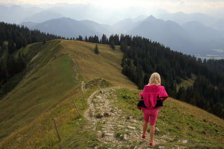 girl is going down on a small mountain path photo