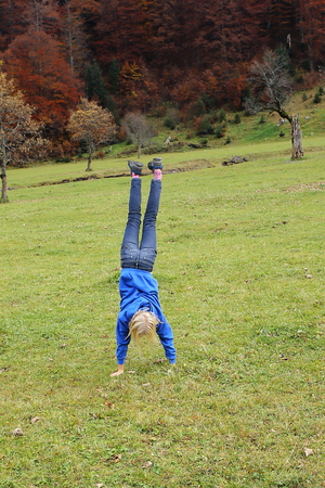 young girl is practising handstand on a field photo