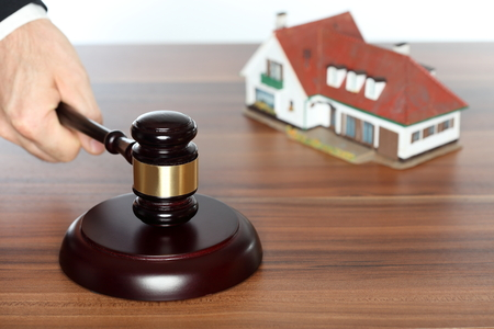 auction symbol with gavel in hand and house in background Stock Photo