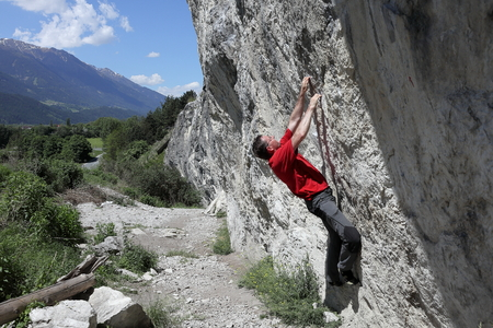 caucasian man is bouldering on a rock wall photo