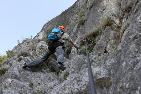 caucasian man is climbing on a rock wall photo