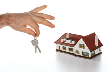 hands are holding a key with house model in background photo