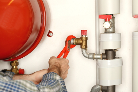 working man with gripper in hand is repairing a heat