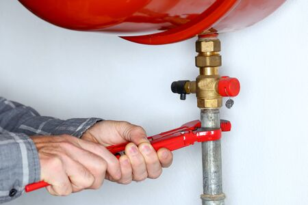 repairman with red gripper is mounting a pipe