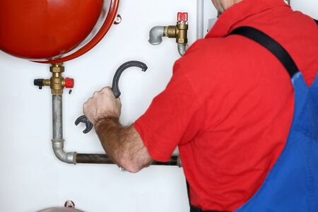 working man with wrench is mounting in heating room Standard-Bild