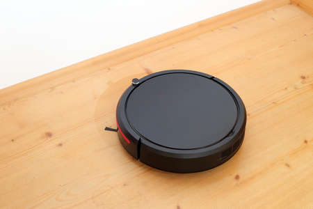 automatic robotic cleaner is cleaning the wooden ground in a house