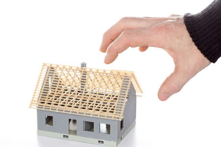 tax symbol with gripping hand and house model