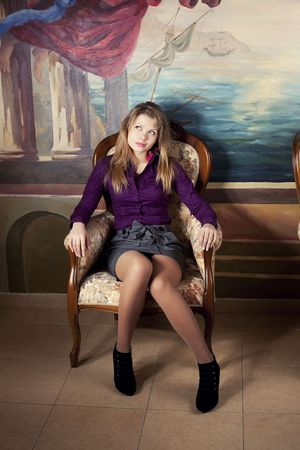 Sexy blond girl  sitting on a luxury armchair