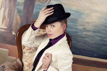 Beautiful young blond woman in black hat. photo