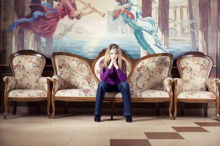 Blond woman waiting on luxury sofa photo