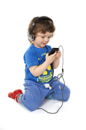 Cute child with headphones and a Mp3 player in hands photo