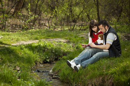 Girl and boy sitting and reading near a river photo