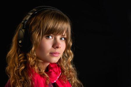 Beautiful young lady with headphones looking at camera photo