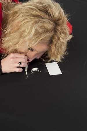 unhealthy living: Blond woman on a tableau of cocaine