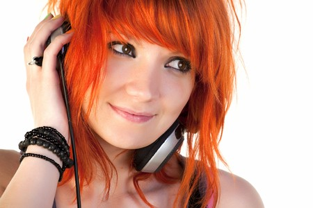 Redhead young woman holding headphones Stock Photo
