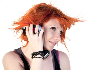 Redhead young woman holding headphones dancing photo
