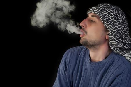 Young man enjoying hookah on a black background Stock Photo