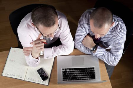 Two businessmen working at laptop photo