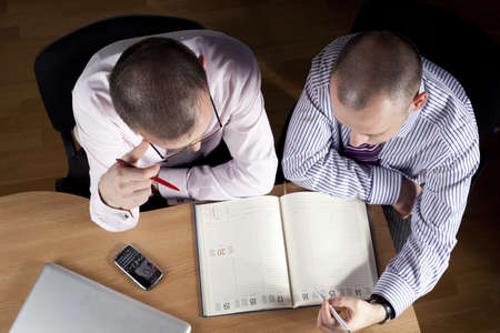 Two businessmen working at notebook photo