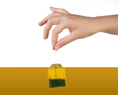 Human hand holding tea bag